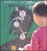 Little boy throwing darts at a picture of an American soldier, Kaesong Youth Park  (image courtesy of Carol Rueckert)