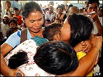 A family grieves during a mass burial in San Jose, Mabini town on south central Bohol island, Philippines, on Thursday, March 10, 2005.