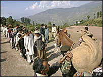 Soldiers unpack mules carrying aid for people in Pakistan-run Kashmir
