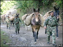 Soldiers lead mules carrying aid for people in Pakistan-run Kashmir