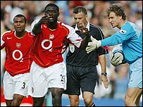 Arsenal players Ashely Cole, Kolo Toure and Jens Lehmann argue with referee Mark Halsey