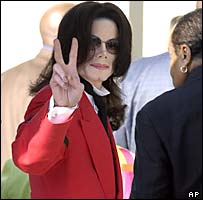 Michael Jackson gestures to supporters as he arrives at court