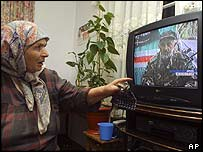 A woman in Grozny watches a news broadcast about the death of Aslan Maskhadov