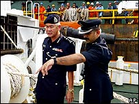 Malaysian police officers inspect a tugboat in Penang island, Malaysia, Tuesday, March 15, 2005.