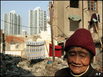 A Chinese woman stands in front of traditional houses about to be demolished in Shanghai, China