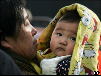 A Chinese woman carries a child on the streets of Beijing, China