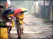 Hondurans walks during a heavy rain from Hurricane Wilma