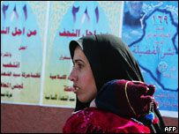 An Iraqi woman walks in front of election posters (file photo)