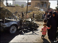 An Iraqi woman and child walk past the remains of a car bomb in Baghdad, Iraq