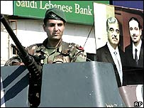 A Lebanese soldier in front of a poster of the slain former PM and his son