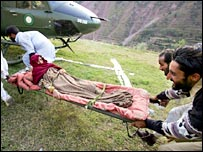 An injured girl is carried to a helicopter in Pakistani-administered Kashmir