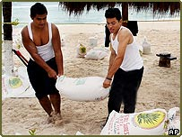 Workers place sandbags at the entrance to a beachside hotel, Playa del Carmen, Mexico