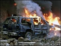 A burning car in the wreckage of the bomb attack that killed Rafik Hariri