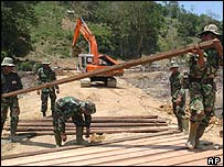 Indonesian soldiers rebuild a bridge in Aceh