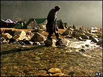 Man crosses a river at a camp near Balakot in Pakistan