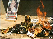Two toy Caterpillar vehicles burning during a Palestinian protest