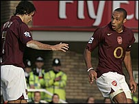 Robert Pires and Thierry Henry exchange words after their penalty blunder