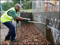 A council worker cleans off graffiti