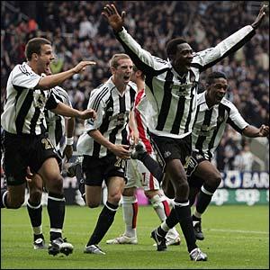 The Newcastle players run to celebrate with Shola Ameobi