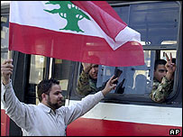 Anti-Syria supporter waves Lebanese flag as Syrian intelligence agents leave their offices in Beirut