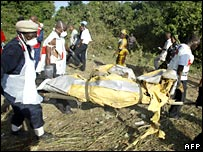 Rescue workers carry the remains of a victim of a plane crash in Nigeria