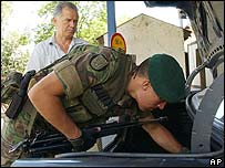 A Nato peacekeeper inspects a car outside Sarajevo, Bosnia