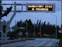 A highway in the Florida Keys is empty as a sign announces that a mandatory evacuation is in progress