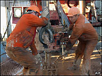 Kazakh workers mine oil near town of Aktyubinsk, Kazakhstan, in this September 2004 file photo