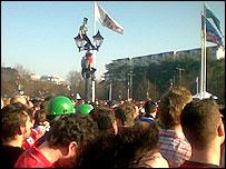Fans climbing a lamppost