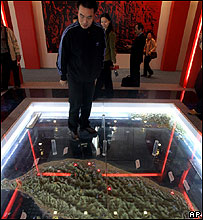 A Chinese visitor walks near a three-dimensional map of Taiwan at a Beijing exhibition, 24 Oct