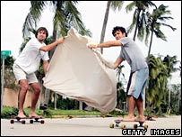 Blake Crawford and Carlos Galceran take advantage of the heavy winds as they skateboard down a street as Hurricane Wilma passes through