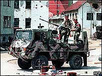 A Bosnian Serb armoured vehicle drives through the deserted streets of Srebrenica in 1995