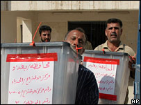 Iraqi election workers carry referendum vote boxes