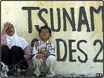 Acehnese woman, cries with her son during the first visit to her village of Ulee Lheu in Banda Aceh, Indonesia