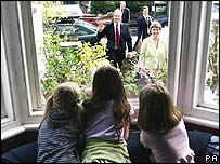 children watch Tony Blair and Ruth Kelly arrive at their home