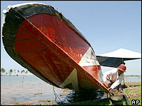 Hasyim, an Acehnese fisherman, cleans his boat in Meuloboh, Indonesia, Friday, March 18, 2005.