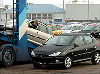 A car being driven onto a trailer at Peugeot's Ryton plant, Coventry