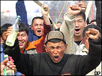 Opposition protestors shout anti-government slogans as they hold bottles with flammable liquid and wooden sticks in Osh, Kyrgyzstan, Monday, March 21, 2005
