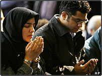 Man and woman sit side by side during Islamic prayers New York