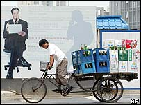 A man hauls a tricycle load of beer past a billboard promoting a commercial complex in Beijing's central business district