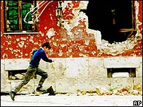 Boy runs in sniper alley in Mostar, 1993
