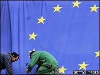 Workmen pin down the EU flag