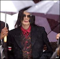 Aides hold umbrellas over Michael Jackson as he arrives at court