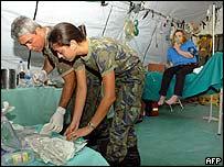 Brazilian military doctors treat a woman in a field hospital