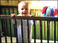 Baby standing up in a cot