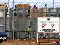 Asylum seekers hold signs stand on the refugee detention centres roof in protest at Woomera in Australia's Outback, Saturday, Jan. 26, 2002.