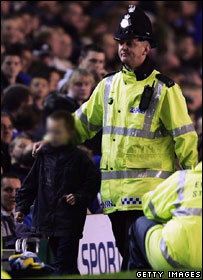 The boy is led off the pitch by a police officer