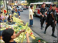 Philippine policemen patrol the vicinity with vendors selling decorative palms for Palm Sunday in front of a major cathedral in the largely-Roman Catholic Philippines, 20 March 2005.