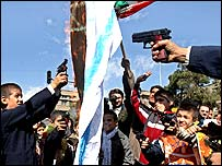 Iranian protesters shoot a burning Israeli flag in Tehran