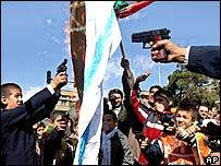 Iranian protesters shoot a burning Israeli flag in Tehran